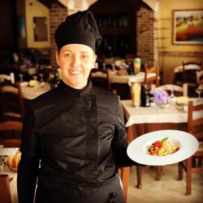 """Emanuela Girotto regge un primo piatto di pasta fresca nella sala del Ristorante All'Angelo """"Da Lalo""""."""