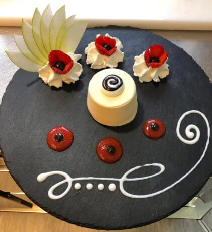 Semifreddo realizzato dai pasticceri di Lalo e servito su un piatto nero decorato con panna fresca fatta in casa.