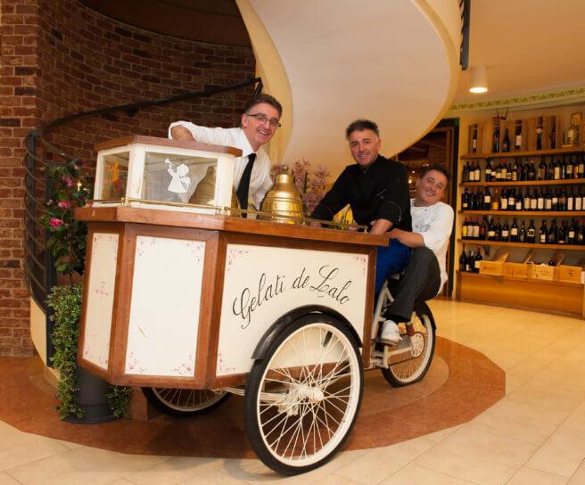 """I fratelli Marco, Valerio e Franco Girotto (da sinistra a destra), in posa sul carretto dei gelati col quale Orlando """"Lalo"""" Girotto diede inizio all'attività."""