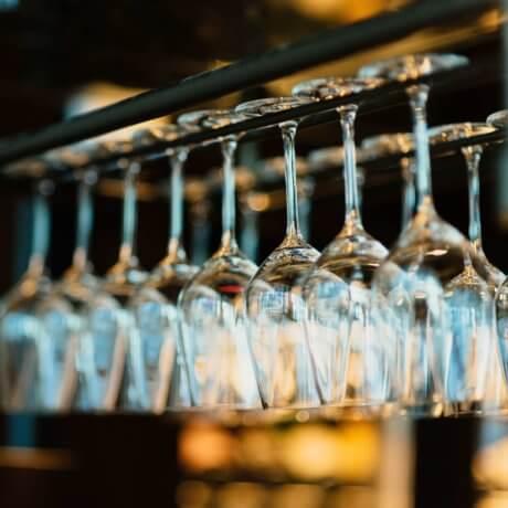 Calici per vino disposti su una rastrelliera. La carta dei vini del Ristorante All'Angelo Da Lalo offre una selezione di bottiglie provenienti da oltre 30 cantine.